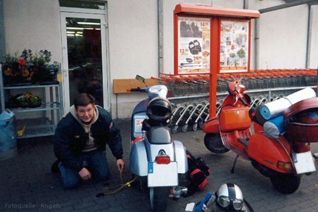 26.07.2002: Ralf beim Bepacken seiner metallicblauen Vespa P200E vor einem Supermarkt auf dem Weg nach Borculo. Daneben die rote Vespa P200E von Angelo. (Foto: Angelo Colapietro)